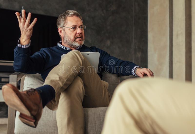 Psychologist talking with patient during the therapy royalty free stock images