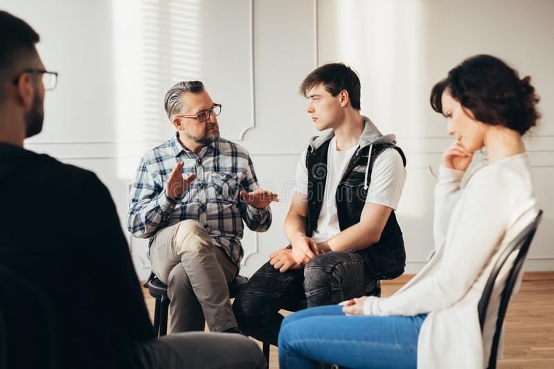 Psychologist talking about twelve-step program to addicted man during group support meeting. Psychologist talking about twelve-step program to addicted men royalty free stock photos
