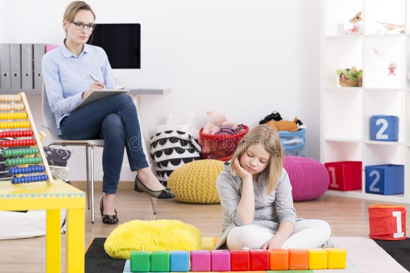 Psychologist testing girl with Asperger`s. Female psychologist testing young girl with Asperger`s syndrome symptoms stock images