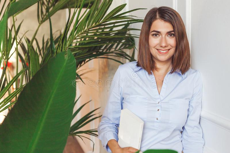 Psychologist woman with book in office with tropical plants royalty free stock images