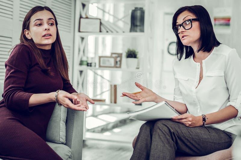psychologue aux cheveux foncés donnant quelques instructions à son client photos libres de droits