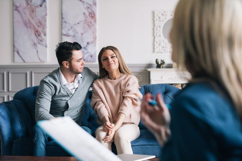 Psychologue de visite de beaux et heureux jeunes couples pour la consultation de relations images stock