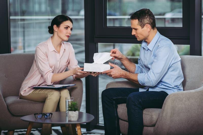 Psychologue donnant la serviette à l'homme d'affaires de renversement photo libre de droits