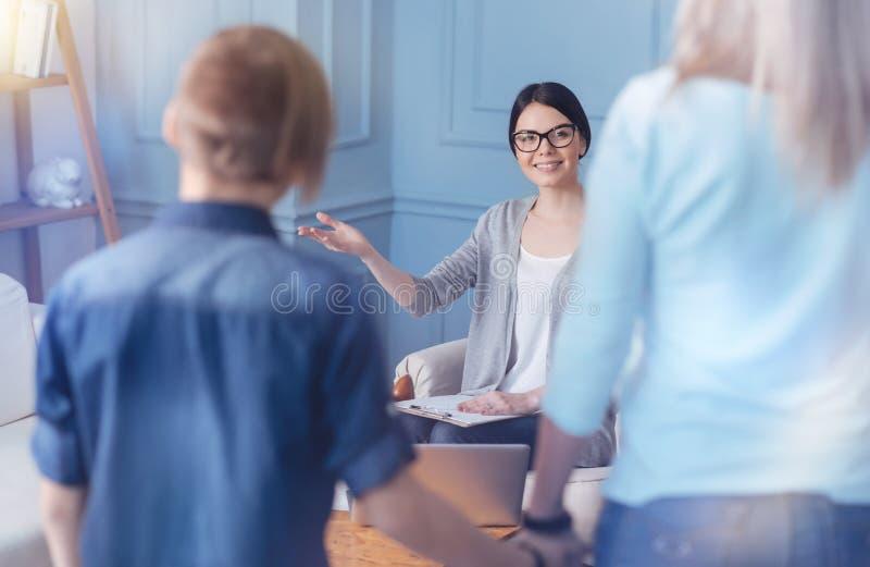 Psychologue féminin de sourire saluant le nouveau patient adolescent et sa maman images libres de droits