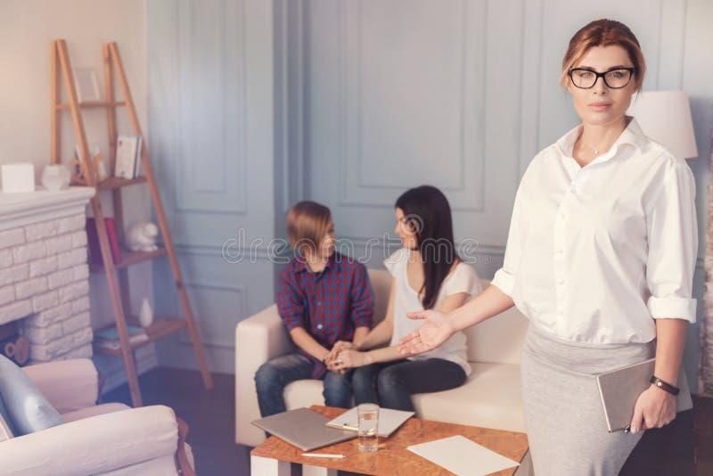 Psychologue féminin utile professionnel se tenant dans son bureau photographie stock libre de droits