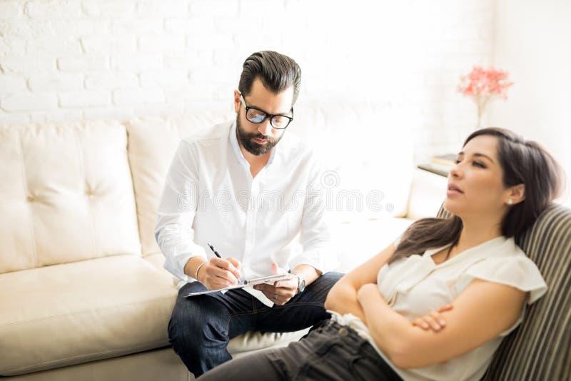 Psychologue faisant des notes pendant la session de thérapie avec le patient photo libre de droits
