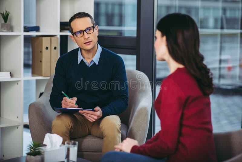 Psychologue masculin écoutant la femme photos libres de droits