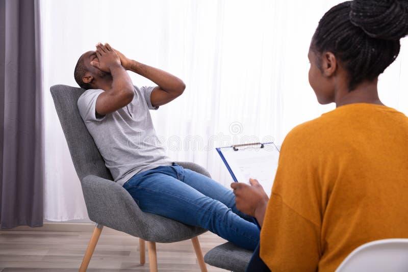 Psychologue Sitting Near Man souffrant de la d?pression photo libre de droits