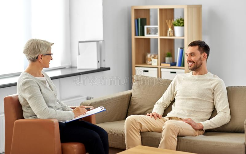 Senior woman psychologist and young man patient royalty free stock images