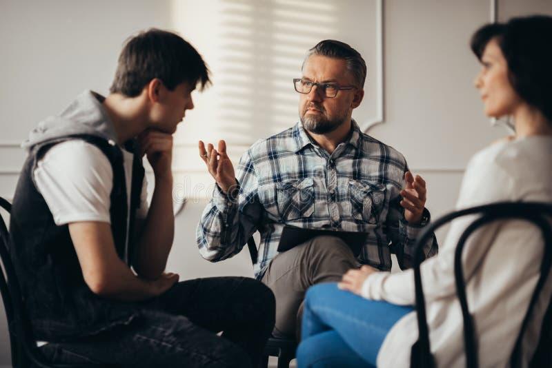 Psycholoog aan gedeprimeerde tiener en zijn mum die tijdens therapiezitting spreken stock afbeelding