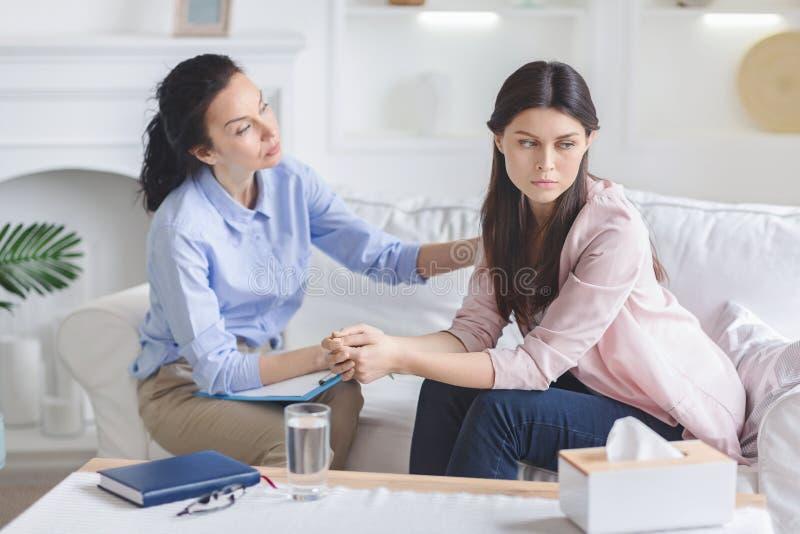 Psycholoog die droevige vrouwelijke patiënt in bureau troosten royalty-vrije stock foto