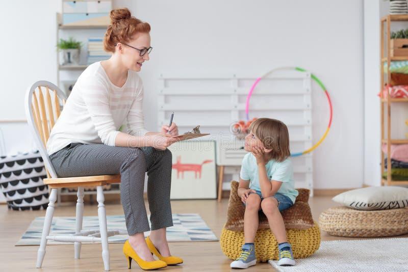 Psycholoog die met weinig jongen spreken stock foto