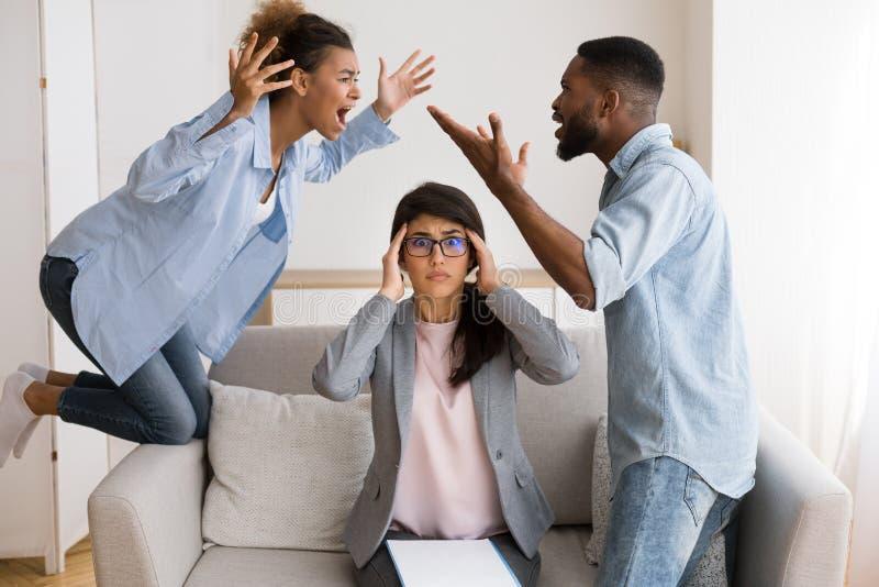 Psychothérapeute choqué observant les conjoints noirs crier et se blâmer photos libres de droits