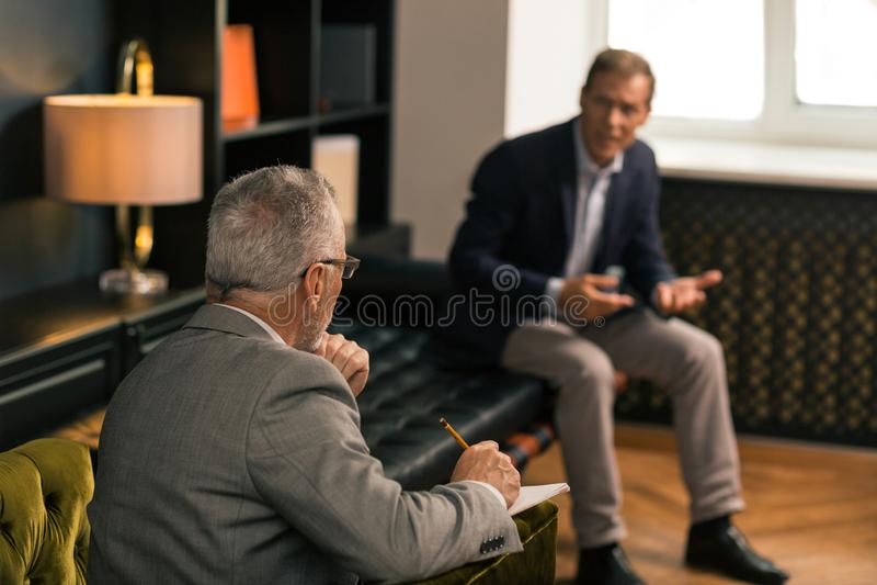 Psychothérapeute faisant des notes et écoutant un patient photo libre de droits