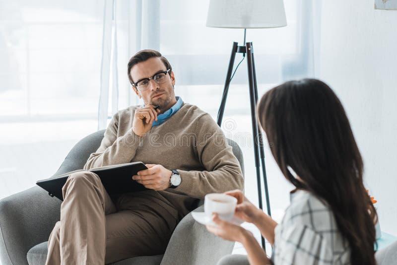 Psychotherapeut, der auf Frau mit Kaffee hört lizenzfreie stockfotos
