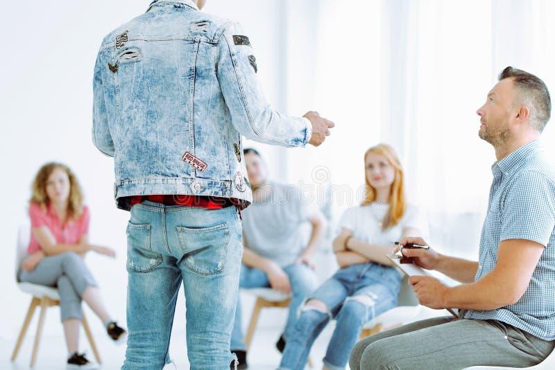Psychotherapeut, der auf jungen Mann hört stockbilder