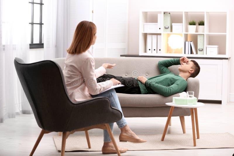 Psychotherapeut, der mit jungem Mann arbeitet stockfotos