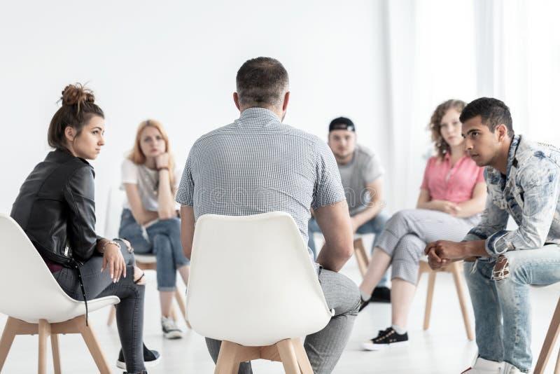 Psychotherapeut, der rebellische Jugendliche während des Treffens von w stützt lizenzfreie stockfotografie
