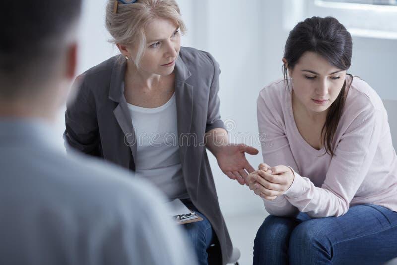 Psychotherapist ondersteunend jonge vrouw stock afbeelding