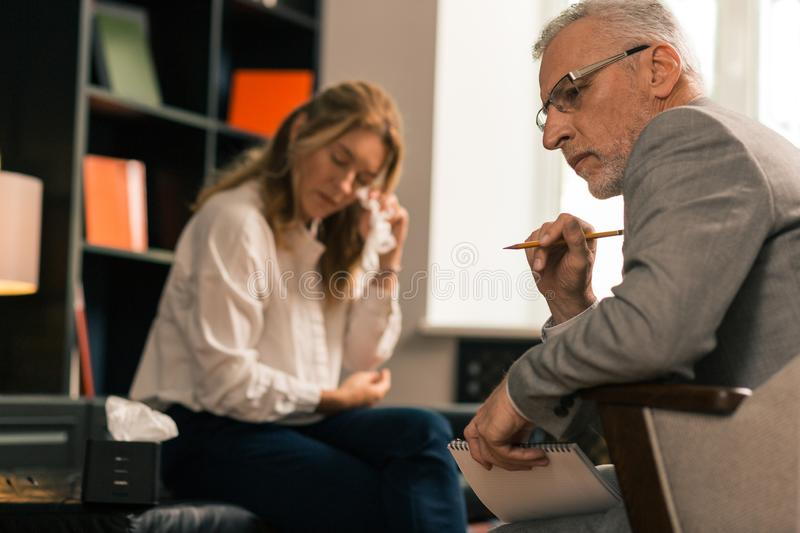 Psychotherapist sitting next to his crying female patient stock images