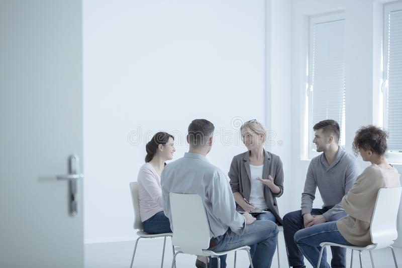 Psychotherapist talking with couples. Psychotherapist talking with a group of couples about how to live in harmony with spouse stock image