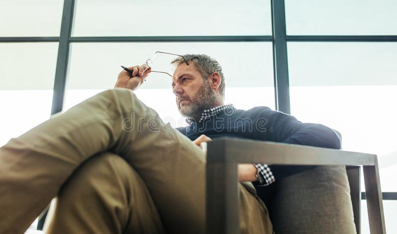 Psychotherapist zitting op wapenstoel in zijn bureau royalty-vrije stock foto's