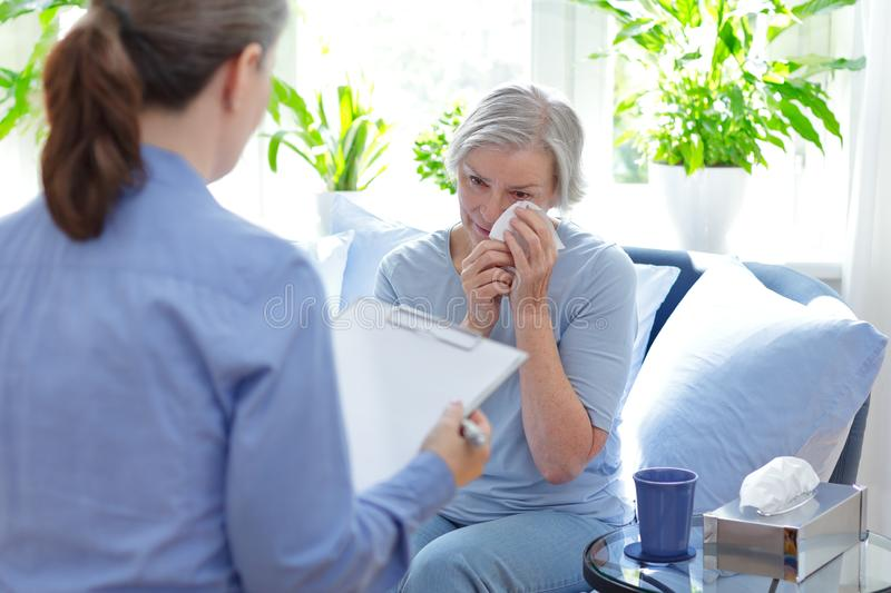 Psychotherapy session senior patient crying stock images