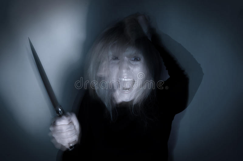 Psychotic Woman with Knife. Deranged psychotic woman with knife for mental health concept with motion blur stock image