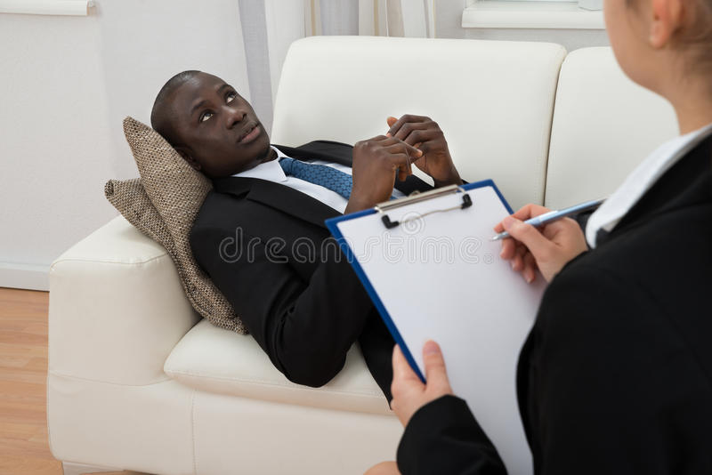 Psykiater Making Notes In Front Of Patient fotografering för bildbyråer