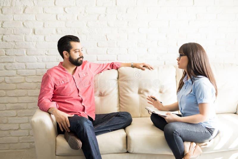 Psykiater som förklarar diagnos och behandling till patienten royaltyfri bild