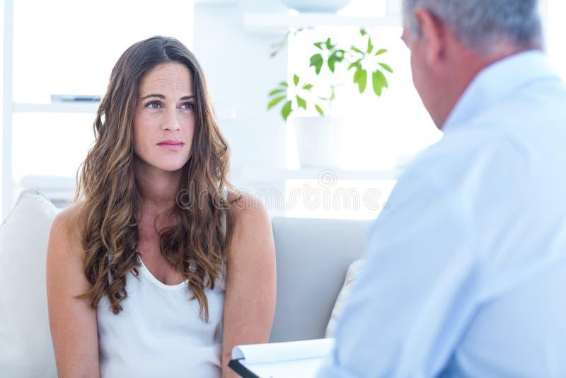Psykiater som råder den kvinnliga patienten royaltyfria foton
