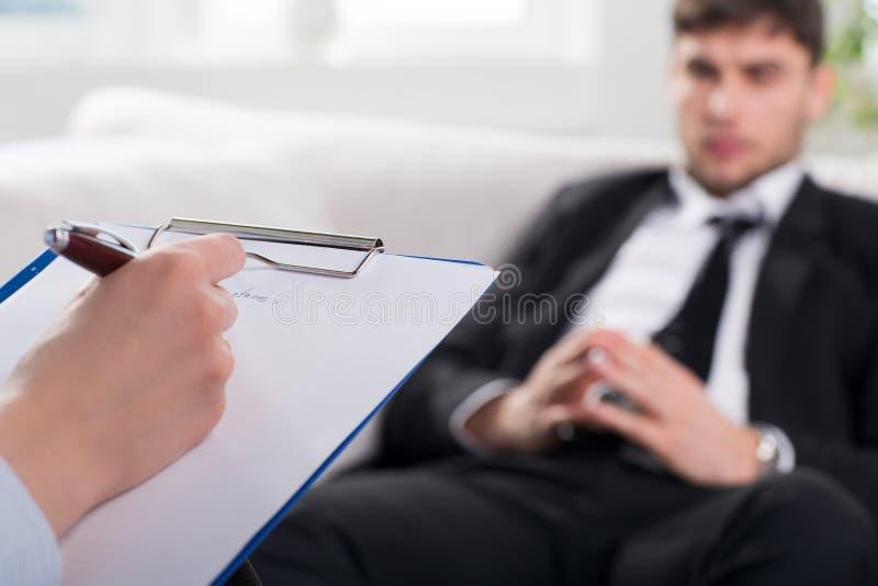 Psykiater som undersöker en manlig patient royaltyfri fotografi