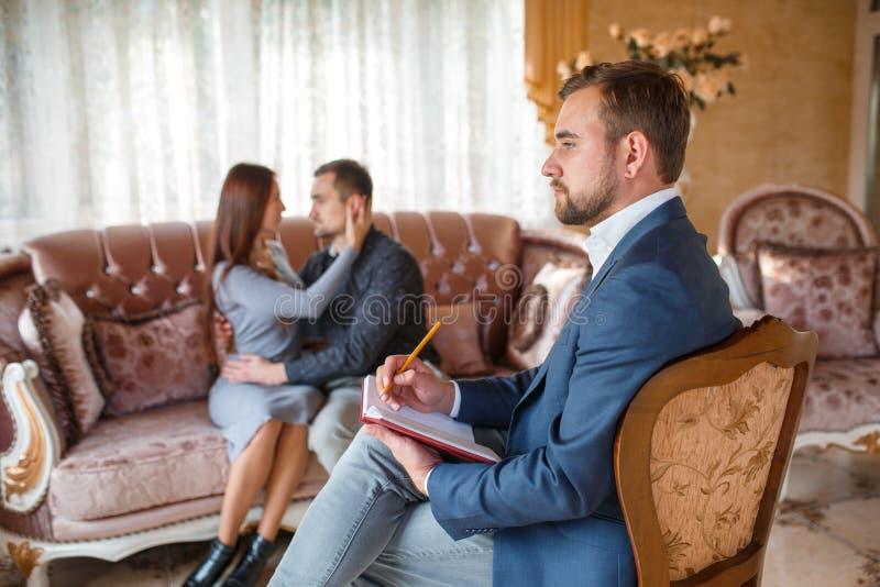 Psykolog med en anteckningsbok på en stol, i bakgrunden ett par på en soffa som ser de royaltyfri foto