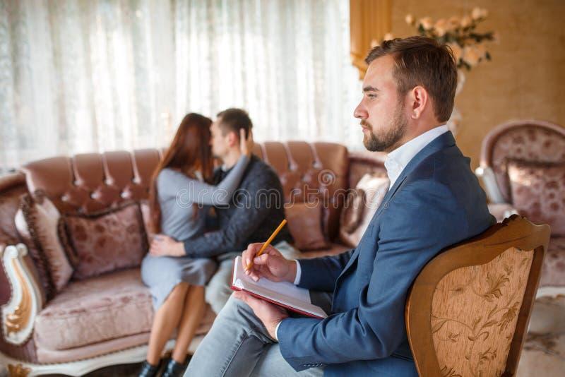 Psykologen med en anteckningsbok på en stol, i bakgrunden ett par på soffan omfamnar royaltyfri foto