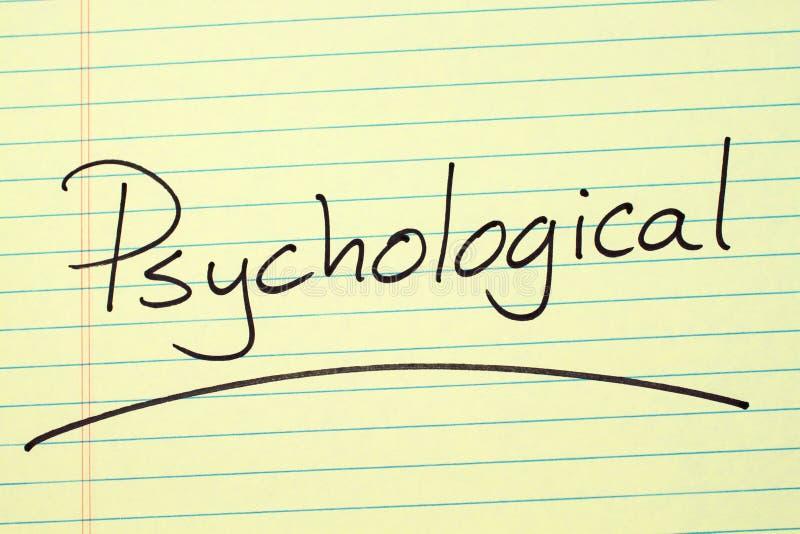 Psykologiskt på ett gult lagligt block arkivfoto