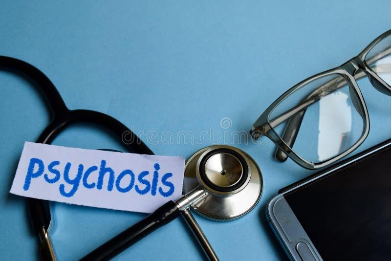 Psykosinskrift med sikten av stetoskopet, glasögon och smartphonen på den blåa bakgrunden royaltyfri fotografi