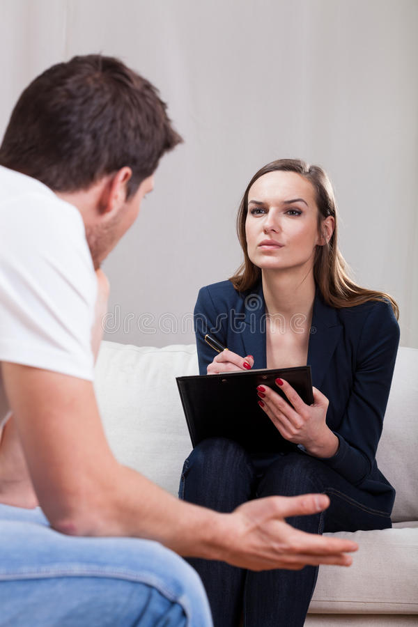 Psykoterapeut som lyssnar till patienten fotografering för bildbyråer