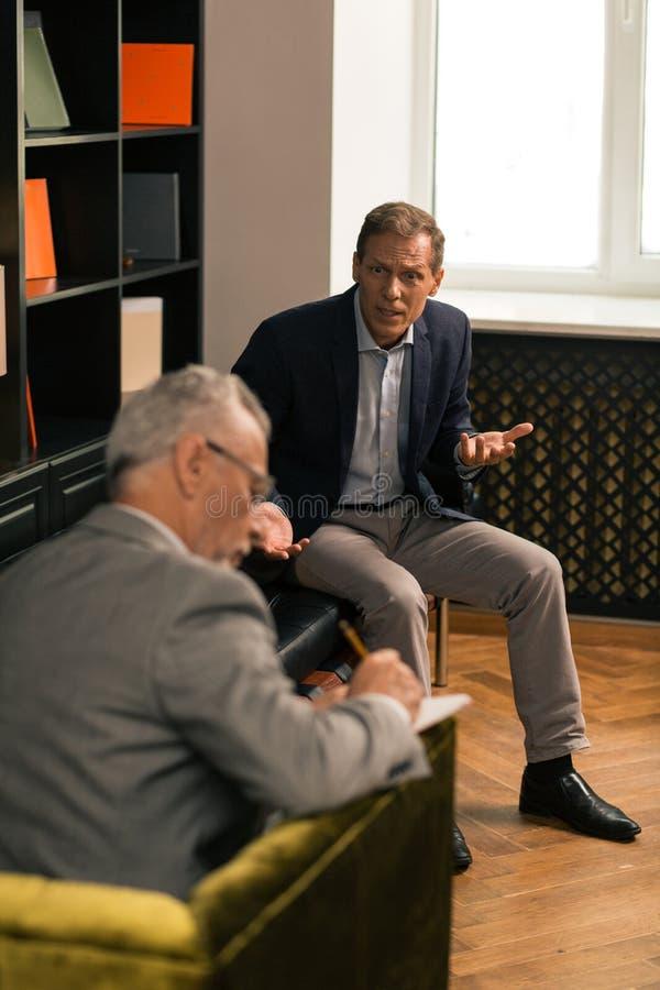 Psykoterapeut som sitter i hans stol, medan ta anmärkningar royaltyfri foto