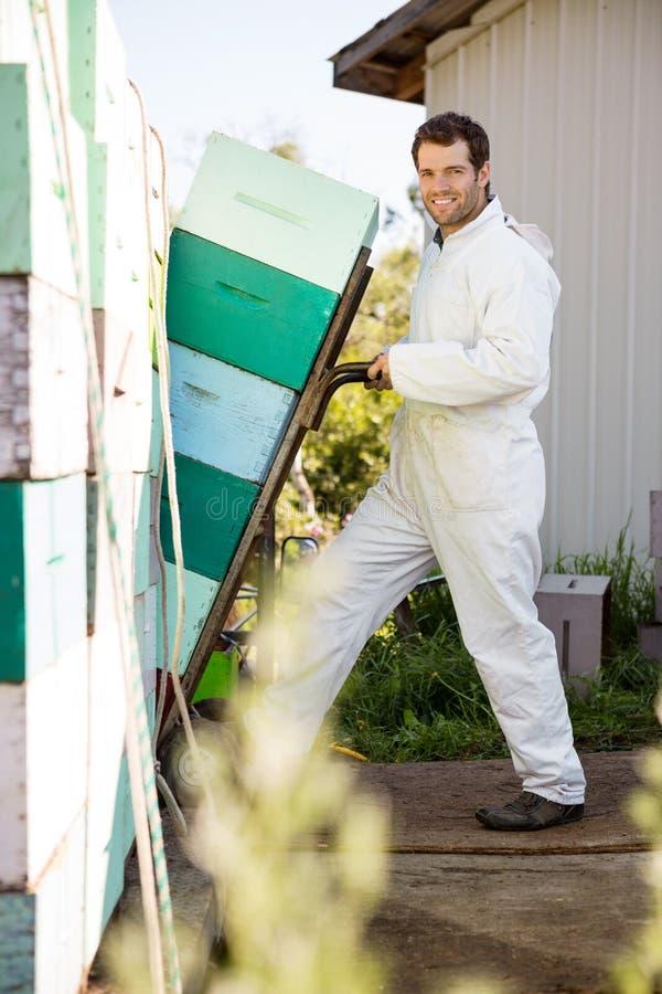 Pszczelarka ono Uśmiecha się Podczas gdy Ładujący Brogującego Honeycomb fotografia stock