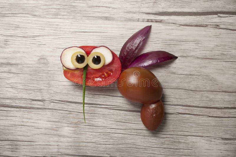 Pszczoła robić z czerwonymi pomidorami na drewnianym tle zdjęcia stock