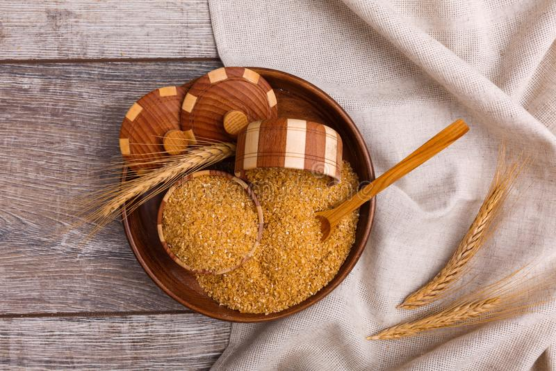 Pszeniczna owsianka w drewnianym talerzu z głębokimi drewnianymi naczyniami na widok zdjęcie stock