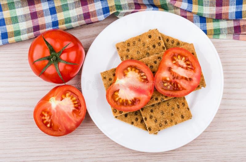 Pszeniczny chrupiący chleb, pomidory i ręcznik na stole, obrazy stock