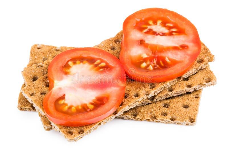 Pszeniczny chrupiący chleb z plasterkiem pomidory odizolowywający na bielu obraz royalty free