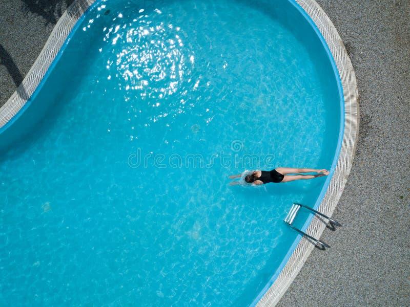 Ptaka oka widok, młoda dziewczyna w czarnym swimsuit, skacze w pływackiego basen zdjęcie royalty free