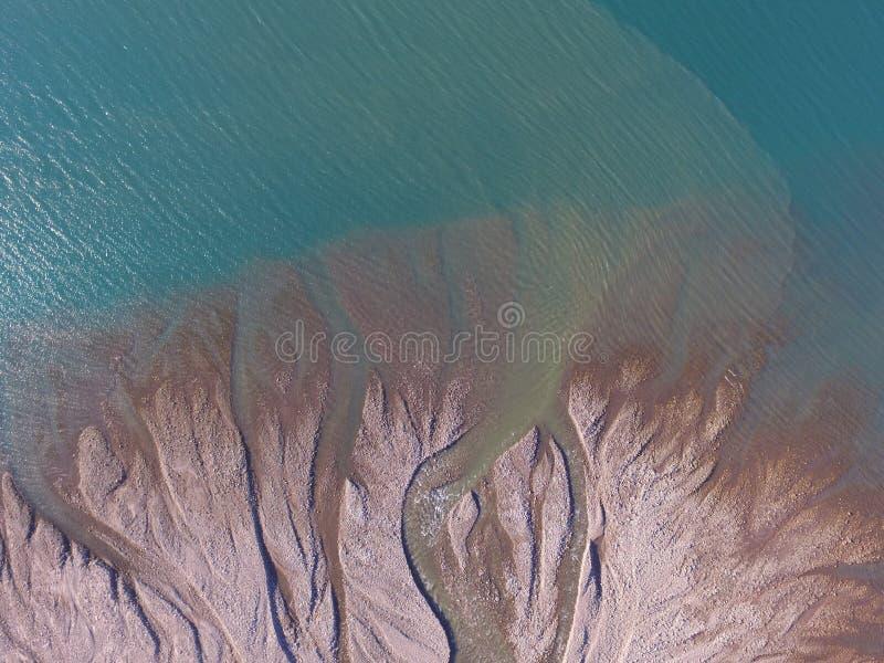 Ptaka oka widok od trutnia fluvial fan i mętny topimy wodę wchodzić do ocean w fjord w północnym wschodzie Greenland zdjęcie stock