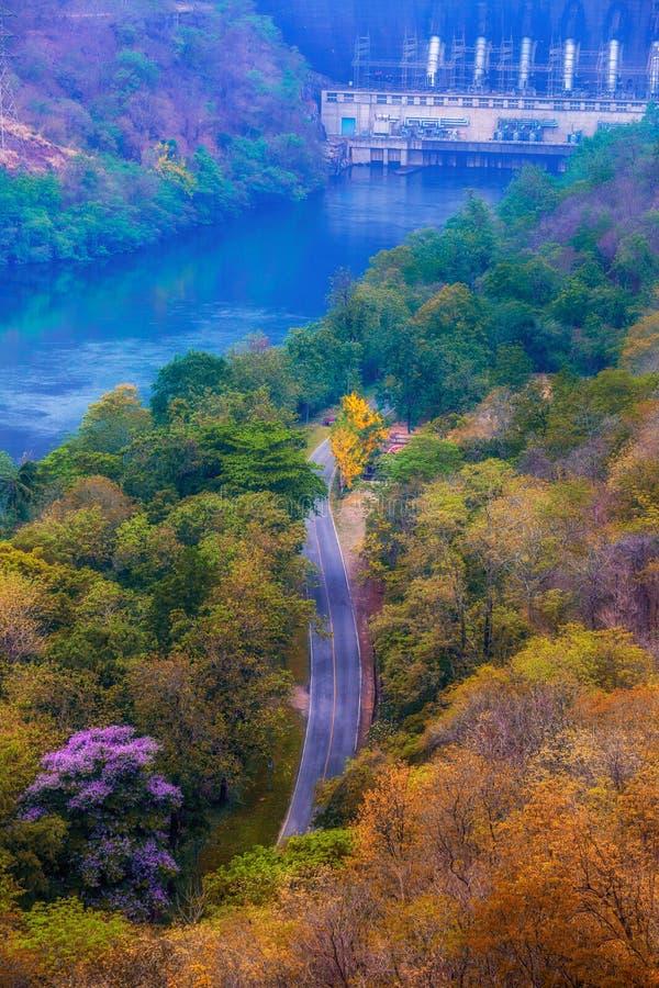 Ptasiego oka widok asfaltowy droga przemian w jesieni mieszam i deciduous forrest z tamą przy wierzchołkiem rzeczny spokoju krajo obraz stock
