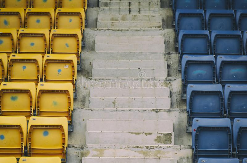 Puści rzędy z błękita i koloru żółtego siedzeniami w na wolnym powietrzu stadium zdjęcie stock