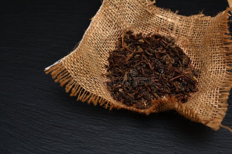 Puñado de hojas de té secas en tablero, la placa o la bandeja negra de la pizarra T foto de archivo
