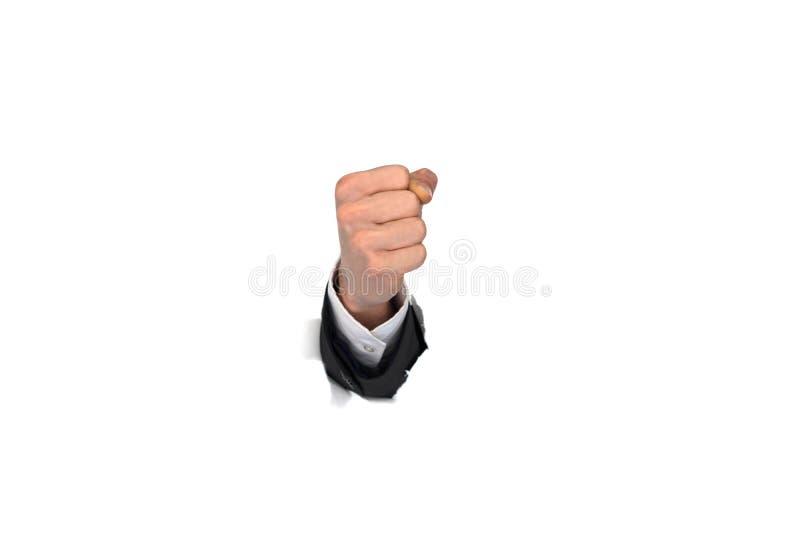 Puño de la mano del hombre de negocios que se rompe a través de la pared de papel imagen de archivo libre de regalías