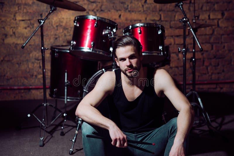 Può il battito essere con voi Ripetizione di concerto rock nel club di musica L'uomo bello si siede in scena allo strumento di pe fotografie stock libere da diritti